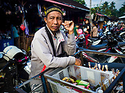 07 AUGUST 2017 - BEBANDEM, BALI, INDONESIA: A snack vendor waits for customes in the market in Bebandem, in far eastern Bali. The market is known for baskets, which are woven in the area. Bali's local markets are open on an every three day rotating schedule because venders travel from town to town. Before modern refrigeration and convenience stores became common place on Bali, markets were thriving community gatherings. Fewer people shop at markets now as more and more consumers go to convenience stores and more families have refrigerators.     PHOTO BY JACK KURTZ