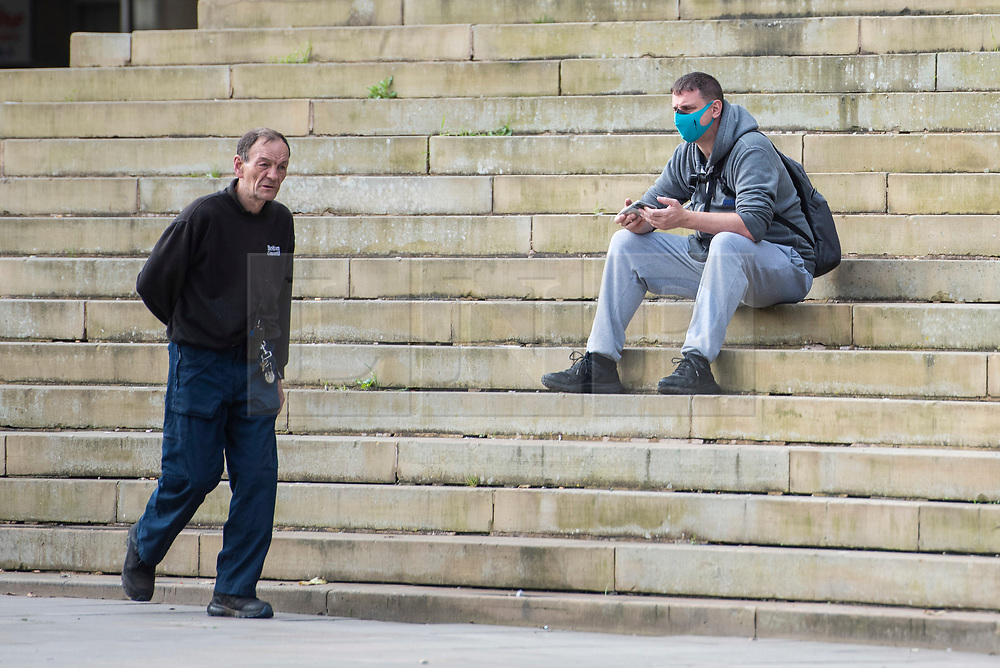 © Licensed to London News Pictures. 04/09/2020. Bolton, UK. A man in a face masks sits on the steps of the Town Hall on a quiet morning in local lockdown in Bolton. Bolton now has the highest infection rate in the UK. Photo credit: Kerry Elsworth/LNP