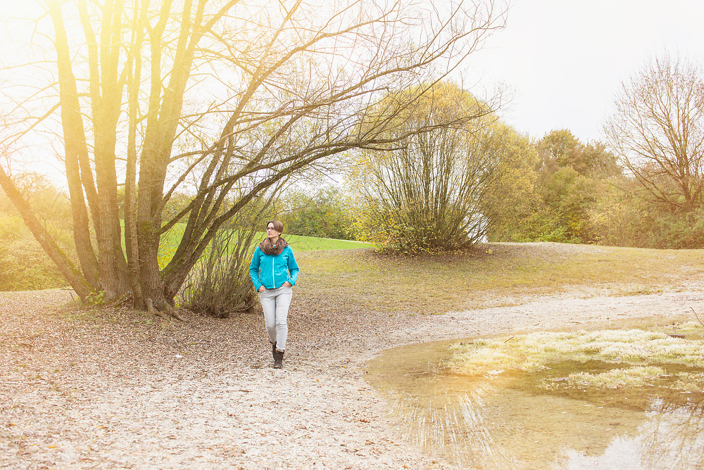 Woman walking at shore of lake by trees in autumn