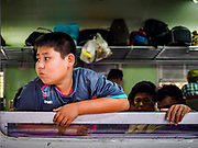 02 JANUARY 2019 - BANGKOK, THAILAND:      A boy on a train in Hua Lamphong Train Station in Bangkok looks out the window of the train. The train and bus stations in Bangkok were crowded Wednesday with people going home after the long New Year's weekend.     PHOTO BY JACK KURTZ