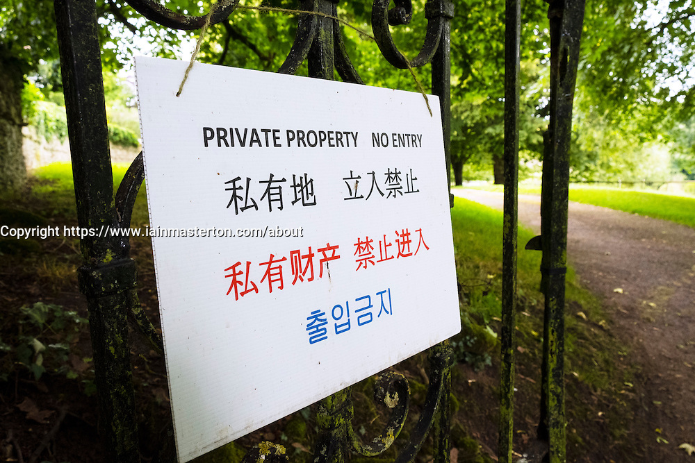 Sign at Arlington Row , Bibury,in the Cotswolds warning of private property in Chinese and Korean, England, United Kingdom