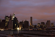 Looking over the East River from the Brooklyn promenade, lights start to come on in Manhattan's financial district, four days after Sandy. Freedom Tower, at 1 World Trade Center, seen on the left with construction cranes at the top, is lit.