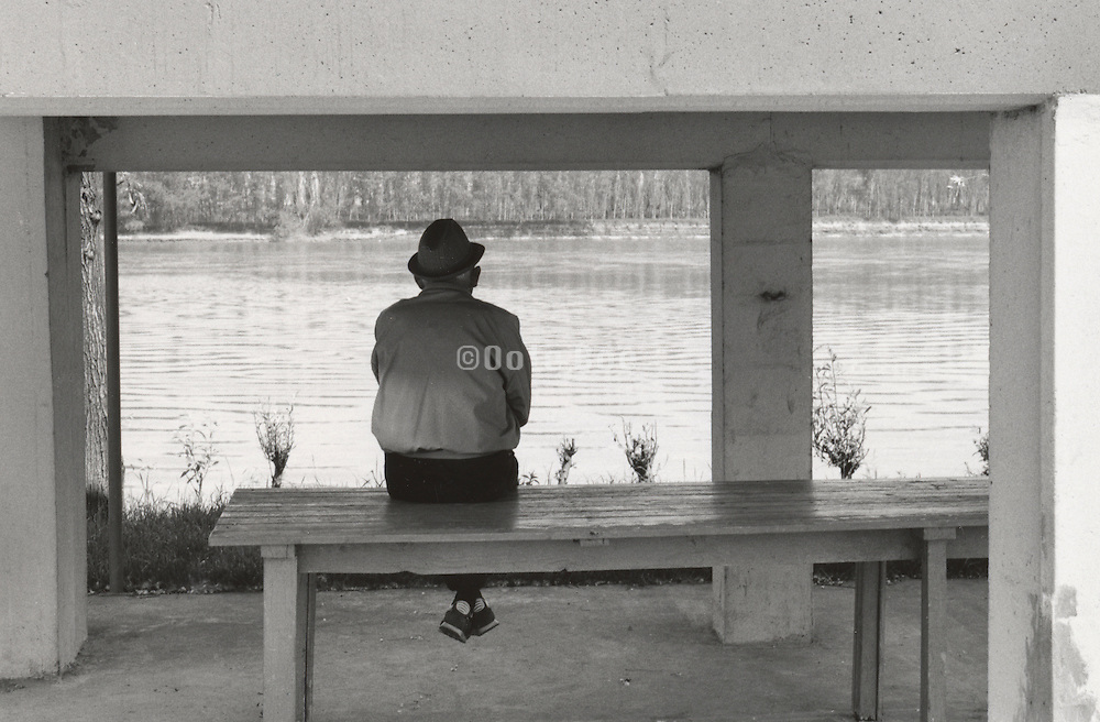 Elderly man sitting by river