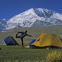 A trekker stretches in an expedition camp in the Pamir Mountains under Mount Mustagh Ata (24,750') in Xinjiang Province of far-western China.