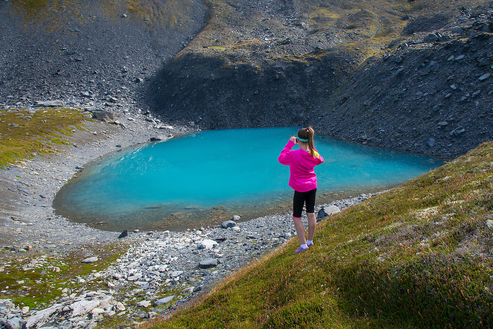 Young hiker enjoys the discovery of a turquoise pothole lake high in the Kenai Mts. above Hope, Alaska PLEASE CONTACT US FOR DIGITAL DOWNLOAD AND PRICING.