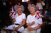 Elderly ladies wave union jack flags and enjoy an afternoon of nostalgia in their local east end pub in east London, remembering the 50th anniversary of VE (Victory in Europe) Day on 6th May 1995. In the week near the anniversary date of May 8, 1945, when the World War II Allies formally accepted the unconditional surrender of the armed forces of Germany and peace was announced to tumultuous crowds across European cities, the British still go out of their way to honour those sacrificed and the realisation that peace was once again achieved. Street parties now – as they did in 1945 – played a large part in the country's patriotic well-being.