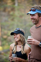 Couple drinking wine while on a whitewater raft trip on the Chilko River. British Columbia, Canada.
