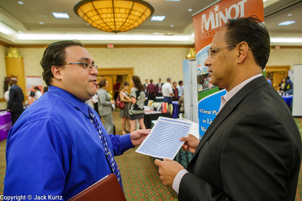 30 JULY 2012 - PHOENIX, AZ:   JOSHUA KOLTER (blue shirt), a job seeker looking for an accounting job, talks to JERRY CHAVEZ, from the Minot, N.D., Area Development Corporation, about job prospects in Minot at the Phoenix Job Fair in Phoenix, AZ. Chavez said there are more than 2400 job openings in Minot, a town of 45,000 in North Dakota. The job fair was sponsored by National Career Fairs, which organizes job fairs across the US. Several hundred people attended the job fair, with some arriving hours before it started. More than 30 employers and prospective employers were conducting interviews at the job fair. There were also resume coaches and educational institutions on site. Arizona is still grappling with the recession. The state's unemployment rate is stuck at 8.2% and the Phoenix metropolitan area has one of the highest home foreclosure rates in the United States.    PHOTO BY JACK KURTZ