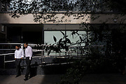 Two south Asian businessmen talk informally outside a City of London office buildingm surrounded with urban vegetation.