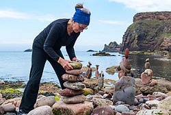 Dunbar, East Lothian, Scotland, United Kingdom 10 July 2021. European Stone Stacking Championship: The first day of the event, which is part of the Edinburgh Science Festival.  Pictured: Caroline Walker, from Edinburgh, competes in the most stones stacked in half an hour competition.<br /> Sally Anderson | EdinburghElitemedia.co.uk