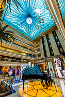 A pianist plays classical music in the beautiful interior of the Zhong Da International Shopping Center on South Street, Xian, China. The mall features stores of well known international luxury brands such as Prada, Louis Vuitton, Georgio Armani and Tiffany.