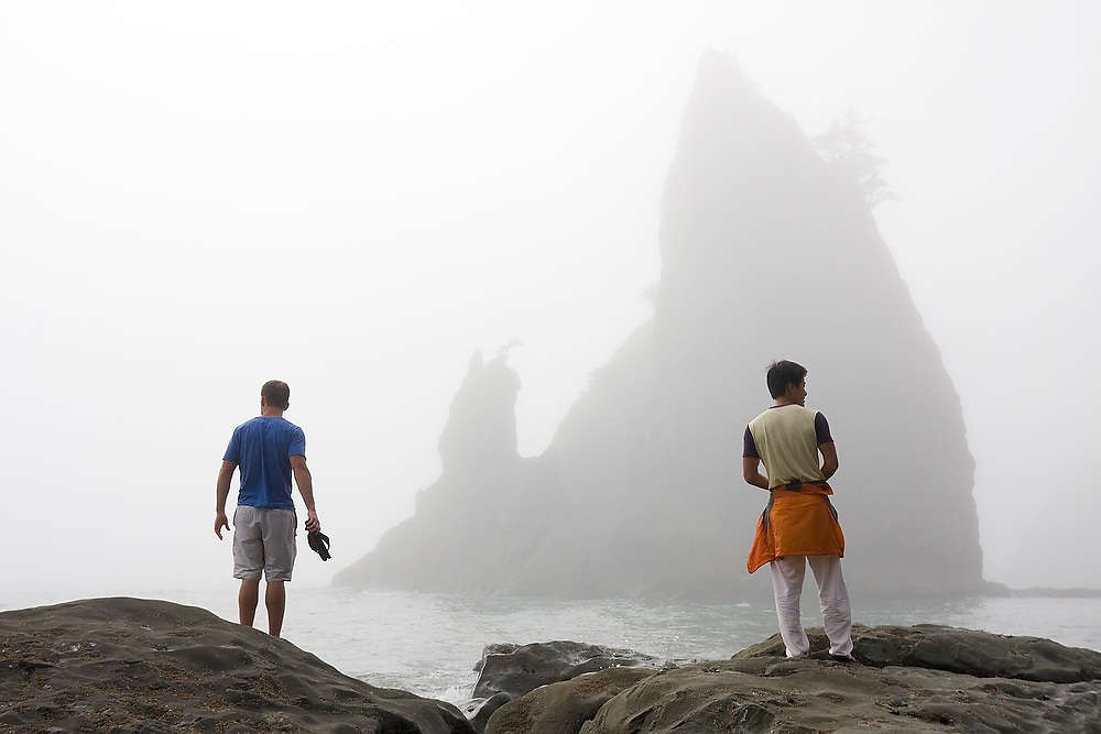 Two men stand facing a large sea stack at Rialto Beach, Olympic National Park, Washington.