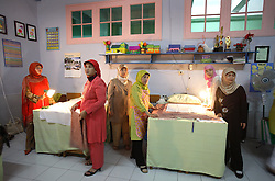Midwives wait for their next circumcision patients in Bandung, Indonesia on April 23, 2006.  The families of 248 girls were given money to have their children circumcised in a mass circumcision celebration timed to honour the Prophet Mohammed's birthday. While religion was the main reason for circumcisions, it is believed by some locals that a girl who is not circumcised would have unclean genitals after she urinates which could lead to cervical cancer. It is also believed if one prays with unclean genitals their prayer won't be heard. The practitioners used scissors to cut the hood and tip of the clitoris. The World Health Organization has deemed the ritual unnecessary and condemns such practices.