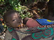 A boy eats honeycomb while his mum digs tubers. At the Hadza camp of Dedauko.