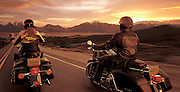 A couple ride their motorcyles alongside of each other while cruising at sunset