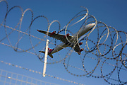 "A Virgin Atlantic Airbus A340 crosses the perimeter fence at Heathrow Airport on its way to an international destination. Seen from below, the passing Jumbo takes-off and climbs under full take-off power over the surrounding airfield security fence. Its razor-wire is an effective deterrent against protesters or terrorists and symbolises the lengths that airport authorities (in this case BAA) need go to to ensure their property is safe. The aircraft is seen almost entangled in the secure wire as if passing through the mesh. From writer Alain de Botton's book project ""A Week at the Airport: A Heathrow Diary"" (2009)."