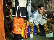 15 OCTOBER 2015 - BANGKOK, THAILAND:  A Chinese opera performer talks on his cell phone before performing at the Vegetarian Festival at the Joe Sue Kung Shrine in the Talat Noi neighborhood of Bangkok. The Vegetarian Festival is celebrated throughout Thailand. It is the Thai version of the The Nine Emperor Gods Festival, a nine-day Taoist celebration beginning on the eve of 9th lunar month of the Chinese calendar. During a period of nine days, those who are participating in the festival dress all in white and abstain from eating meat, poultry, seafood, and dairy products. Vendors and proprietors of restaurants indicate that vegetarian food is for sale by putting a yellow flag out with Thai characters for meatless written on it in red. The shrine is famous for the Chinese opera it hosts during the Vegetarian Festival. The operas are free.   PHOTO BY JACK KURTZ