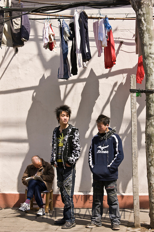 Teenagers stand by a man sleeping in Zi Zhong Road, old French Concession Quarter in Shanghai, China