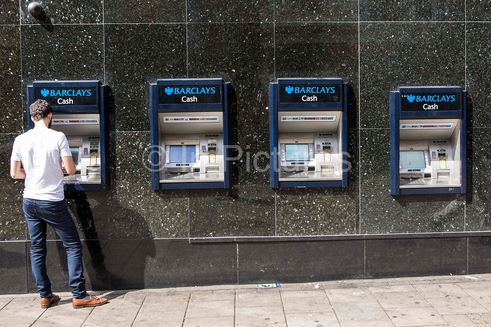 A British man withdrawing money from a Barclays cash machine on a street in London, United Kingdom. These machines are called automated teller machine (ATM) or automated banking machine (ABM).  People are able to access their bank account to withdraw cash, debit card cash advances, check account balances and purchase pre-paid mobile phone credit. Barclays i