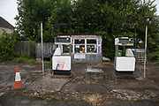 Old fashioned derelict service station and petrol pumps in Warwickshire, UK.