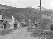 """9707-H02. """"Skagway, in the time of Soapy Smith, Sixth Avenue. Soapy Smith's saloon one of the two low buildings at left"""" (caption on negative envelope) """"Holly Street, Skagway. Showing Soapy Smith Saloon and Frannie Belmont's house. C. L. Andrews"""