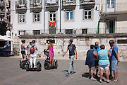A group of Segway tourists stop to hear their guide describe the city next to a crowd of pedestrians in Lisbon, Portugal.