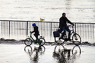 flood of the Rhine on February 4th, 2021, child and adult riding bicycles through the water on the flooded bank of the Rhine in Deutz, Cologne, Germany.<br /> <br /> Hochwasser des Rheins am 4. Februar 2021, Kind und Erwachsener fahren mit Fahrraedern durch das Wasser am ueberfluteten Rheinufer in Deutz, Koeln, Deutschland.