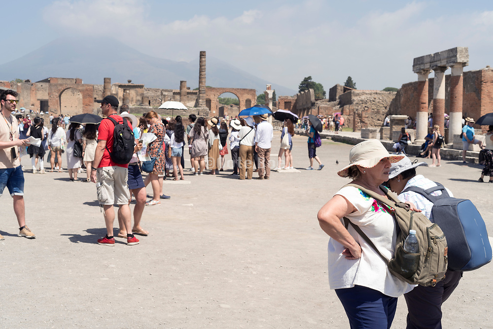 tourists at Pompeii with Mount Vesuvius in the background Italy