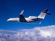 Gulfstream G-V business jet flying over the clouds
