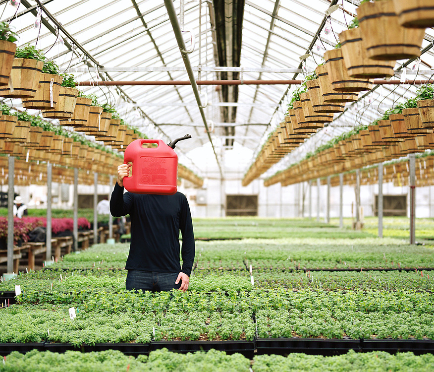 30's man obscuring face with a gas can while standing in a greenhouse.