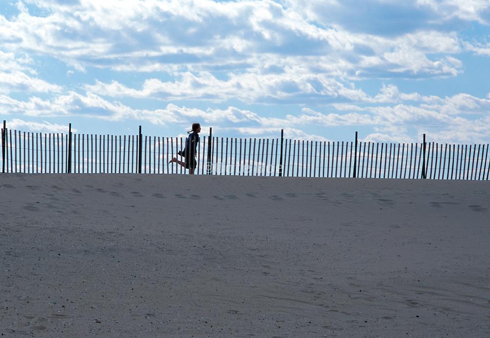Child running through sand dunes on the beach