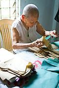 92 year old, Huong Phung makes paper clothes to burn for prayer at the Chua Dieu Vien Pagoda, Hue, Vietnam.  Photo by Stan Olszewski/SOSKIphoto