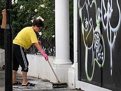 © Licensed to London News Pictures. 27/08/2019. London, UK. A woman cleans dirt and rubbish from the front door of her property in Notting Hill, west London, in the aftermath of the 2019 Notting Hill carnival. The two day event is the second largest street festival in the world after the Rio Carnival in Brazil, attracting over 1 million people to the streets of West London. Photo credit: Ben Cawthra/LNP