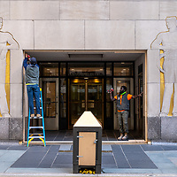 Workers boarding up and entrance at Rockefeller Center in anticipation of post-election violence in New York City, NY USA.