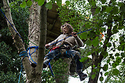 An HS2 Rebellion tree protector moves across lines fixed between trees at Denham Protection Camp on 7 September 2020 in Denham, United Kingdom. Anti-HS2 activists continue to try to prevent or hinder works on the controversial £106bn high-speed rail link for which the start of the construction phase was announced on 4th September from a series of protection camps based along the route of the line between London and Birmingham.