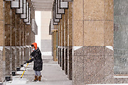 29 DECEMBER 2020 - DES MOINES, IOWA: A worker shovels the snow off the sidewalk in the portico of a downtown Des Moines office building during the heaviest snowfall so far of the 2020-21 winter. Des Moines was expected to get about 8 inches of snow before Wednesday morning. Statewide, across Iowa, more than 900 snowplows have been called out to clear the roads.       PHOTO BY JACK KURTZ