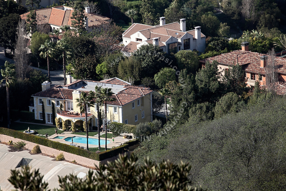 Two men are spending time next to the swimming pool in the garden of a large mansion visible from the scenic Mulholland Drive, running on the hills of Los Angeles, California, USA.