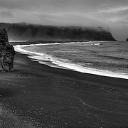 "The beautiful black sand beach of Reynisfjara includes the signature formation Reynisdrangar in the distance and Arnardrangur (""Eagle rock"") on the left."