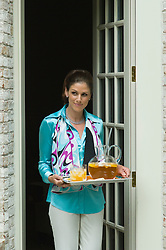 Woman carrying a tray with a pitcher of iced tea and glasses