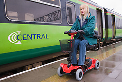 Woman driving electric mobility scooter alongside a train on a station platform,
