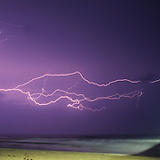 Lightning flashes over Johnie Mercer's Pier in Wrightsville Beach, NC during a summer thunderstorm.