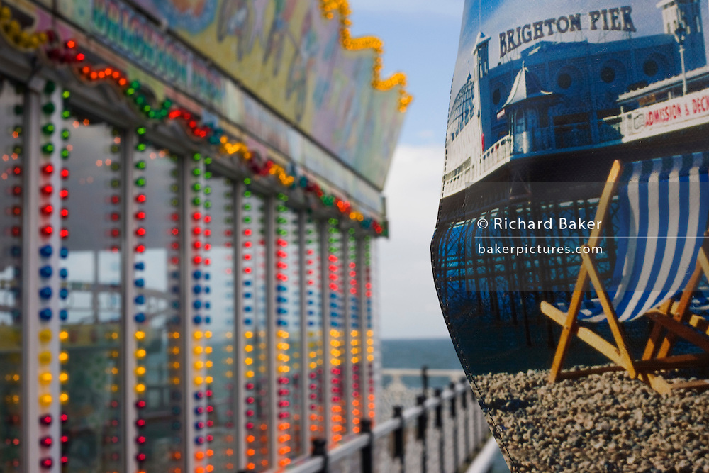 Brighton pier amusement arcade lights and canvass beach deck-chair illustrations with the sea horizon beyond.