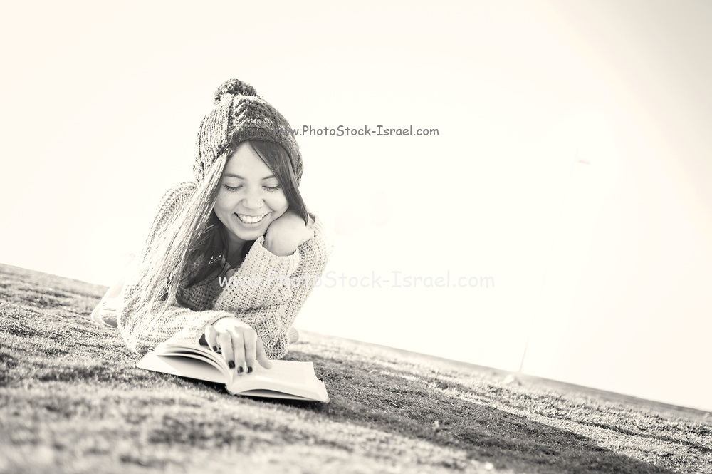 Young 25 year old woman enjoys herself while reading a book alone in the park