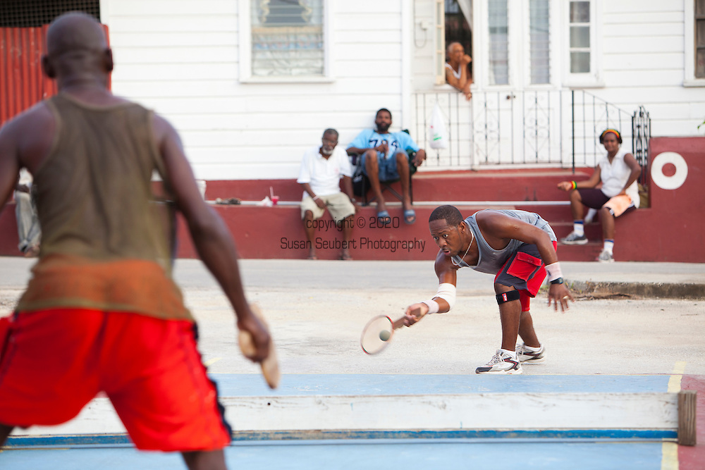 """Originating in Barbados in the 1930s, Road Tennis is played in on the back streets and roads of the country or now in permanent courts, such as the ones in Oistins and Speightstown.  The game is played on a 10x20 foot court and the """"net"""" is an 8 inch by 10 foot piece of wood.  It has the same rules as table tennis (ping pong) and is a 21 point game.  It uses hand hewn rackets made largely from plywood and tennis balls that have had the fur removed.  It is the only endemic sport to Barbados and is wildly popular among the local population.  Pictured here is the Road Tennis Court outside of Speightstown."""