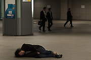A Japanese homeless man sleeps on the floor in the shopping arcades under Tokyo Station, Tokyo, Japan Friday January 30th 2015.