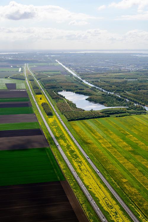 Nederland, Flevoland, Lelystad, 07-05-2015; rijksweg A6 tussen Lelystad en Almere. Voorjaar met de gele bloemen van het raapzaad. Rechts Oostvaardersplassen.<br /> Motorway through the new polder and the yellow flowers of rapeseed in spring.<br /> <br /> luchtfoto (toeslag op standard tarieven);<br /> aerial photo (additional fee required);<br /> copyright foto/photo Siebe Swart