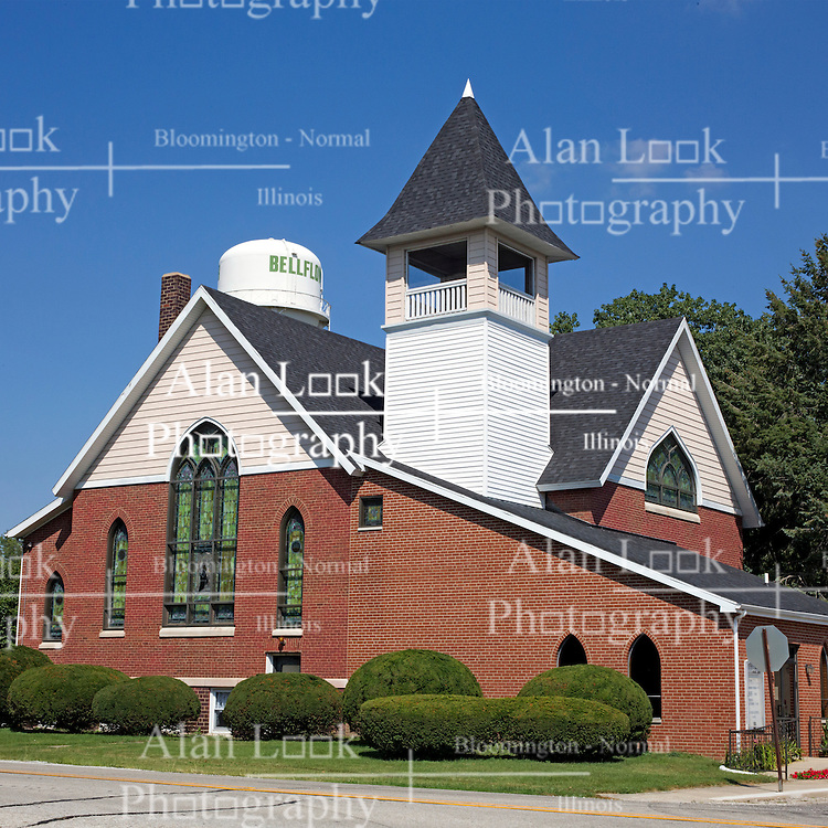 23 August 2013:   A beautifully kept church complete with a belfry and a brick and wood clapboard facade is pictured against a blue sky and the towns water tower in the town of Bellflower in eastern McLean County in Illinois.<br /> <br /> <br /> This image was processed using HDR (High Dynamic Rage) or Panoramic Stitching processes.  It should not be used as an editorial photo unless noted or captioned as an illustration.