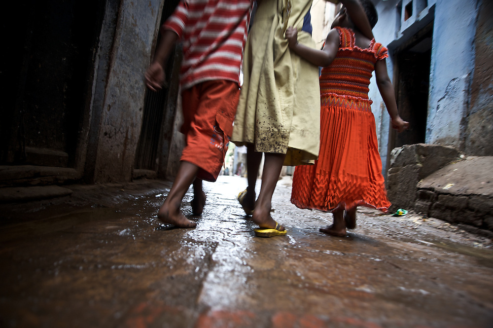 I saw these kids wandering through the gullies, or alleyways, on the way towards their home in Varanasi.  I began following them and wanted to capture the essence of their bare feet and mud stained clothes along the stone pathways.