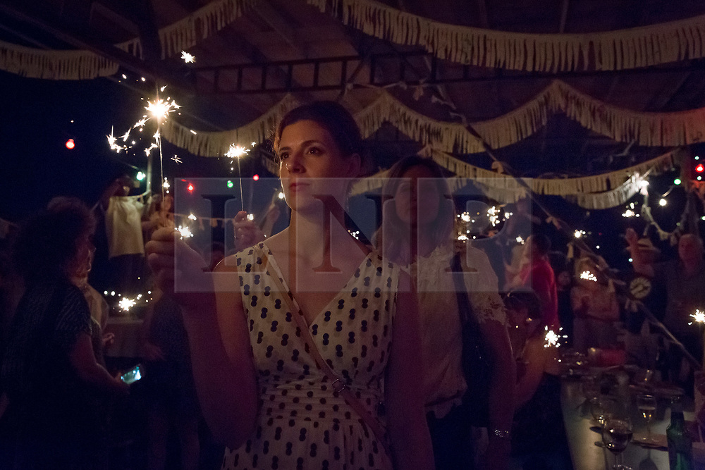 © Licensed to London News Pictures. 18/06/2017. LONDON, UK.  People take a minute silence with sparklers to remember Jo Cox at The Great Get Together at Tower Bridge Moorings in London last night, 17th June 2017. Friends and residents from Hermitage Moornings, where Jo Cox lived on a houseboat with her husband and two children visited residents and friends at Tower Bridge moorings on the River Thames. Photo credit: Vickie Flores/LNP
