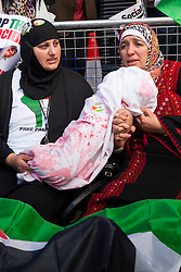 """London, August 23rd 2014. Two women hold a """"bloodstained"""" bundle of cloth symbolising a dead baby as hundreds of protesters outside Downing Street demand that Britain stops arming Israel."""